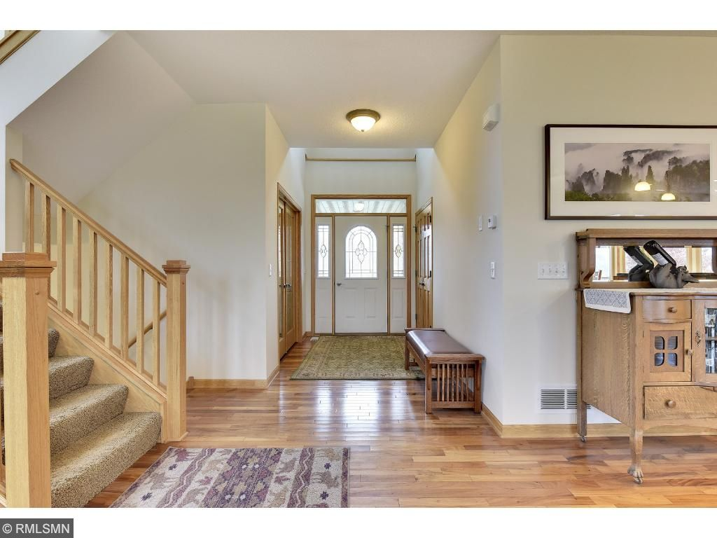 Inviting foyer to greet your guests with tiled and hardwood floors.
