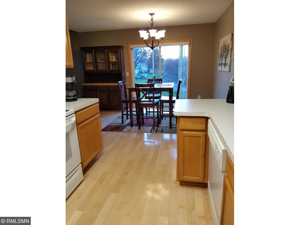 Dining room with hardwood floors that walks out to patio area.
