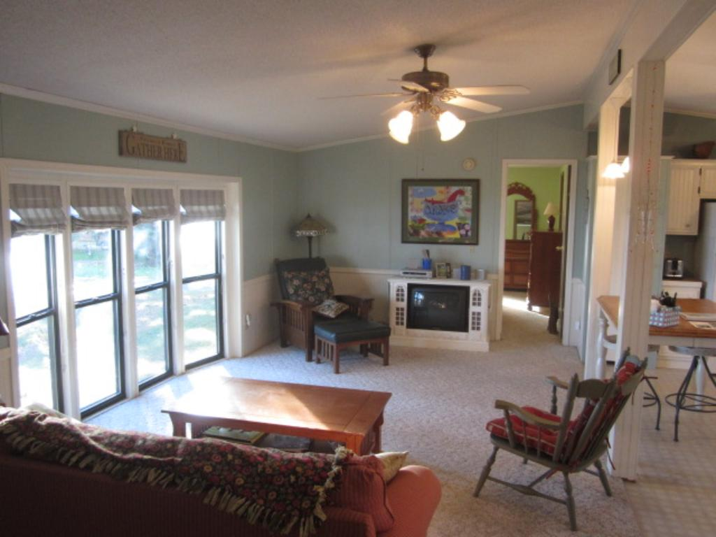 This living room area has a wall of windows overlooking the lake and provides a fresh and clean experience when you come to the lake to relax...in the evenings this place is very warm and inviting inside. The doorway in back of room is to master BR.