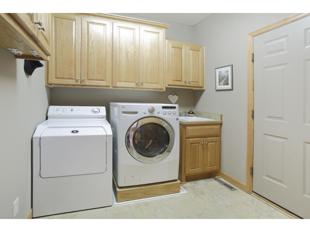 Main floor laundry with cabinets and utility sink.