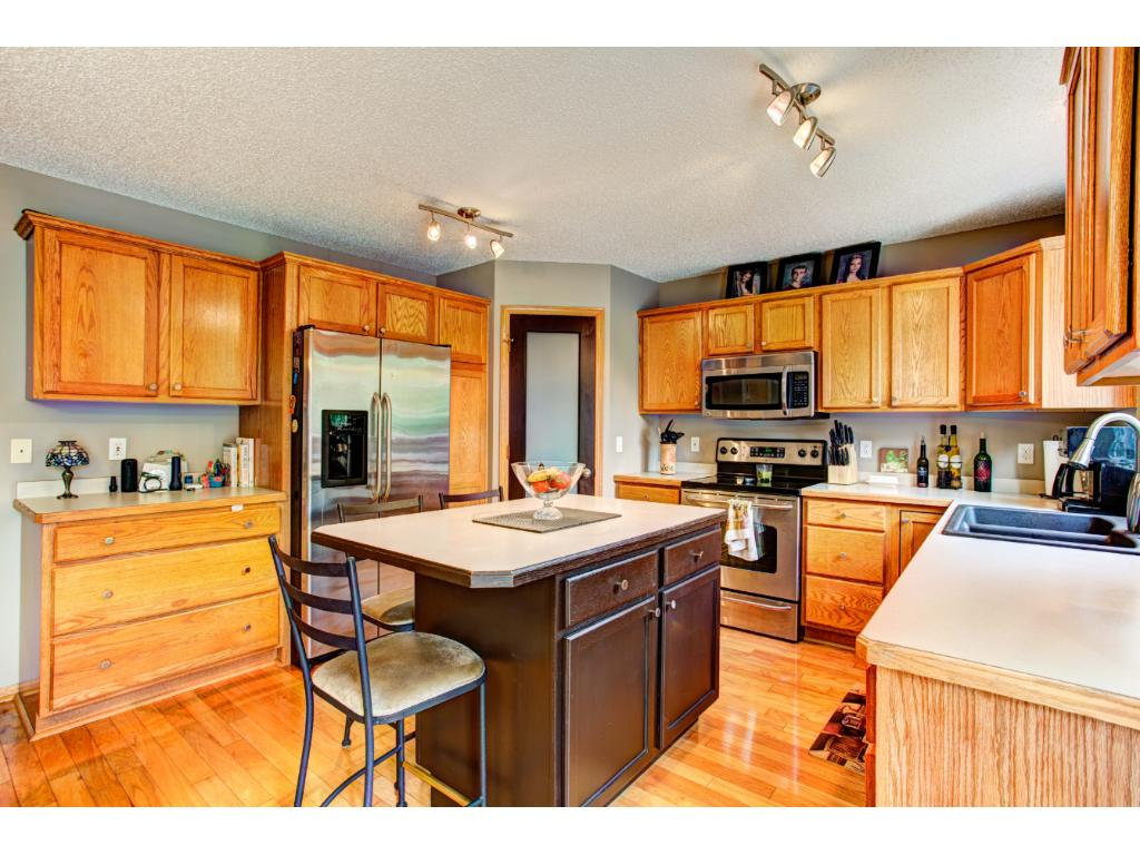 Beautiful and light-filled eat-in Kitchen features gleaming hardwood floors, oak cabinets, center island breakfast bar, planning desk, and bayed dinette with door to the deck