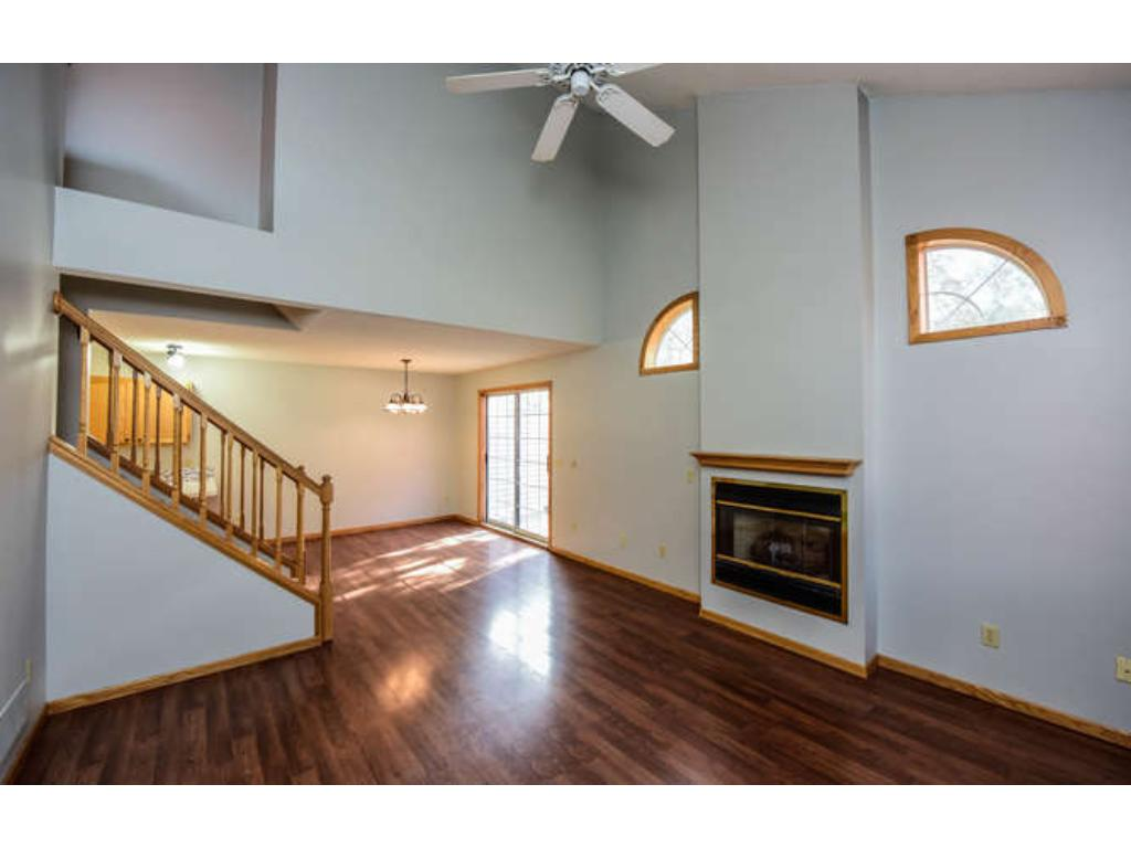 Two story living room with gas fireplace, ceiling fan, and transom windows.