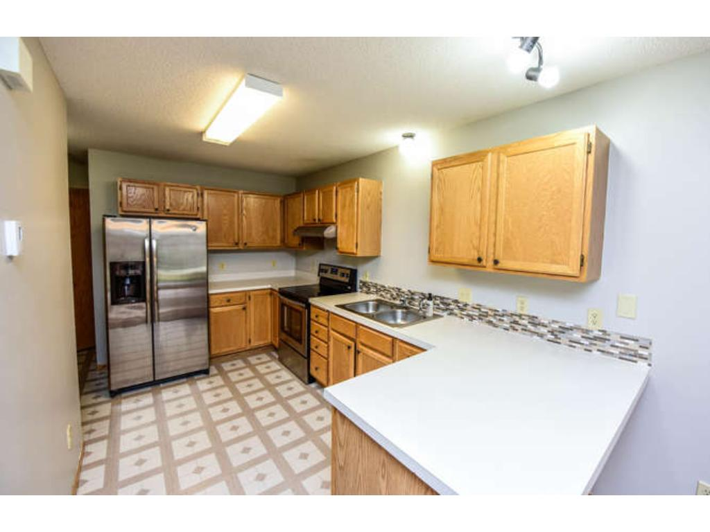 Kitchen with breakfast bar along with brand new stainless steel appliances and back splash.