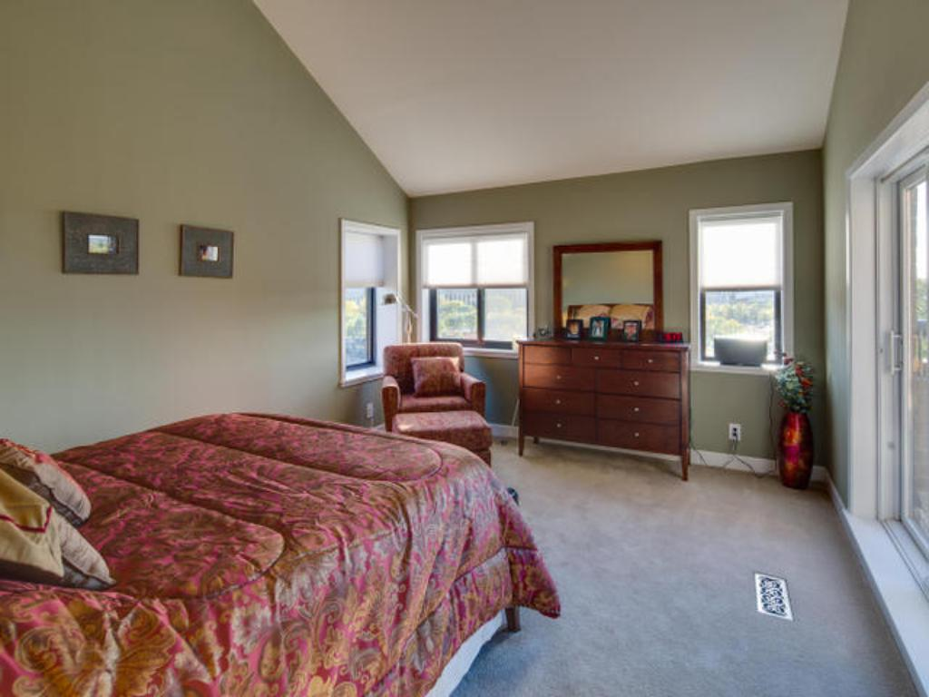 Master bedroom has vaulted ceilings with windows overlooking Downtown Minneapolis skyline and historic cobblestone streets of St Anthony Main and Riverplace