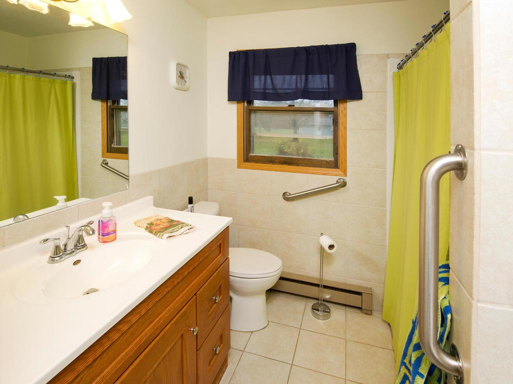 Main level bathroom with a stackable washer and dryer for a convenient main level laundry center.