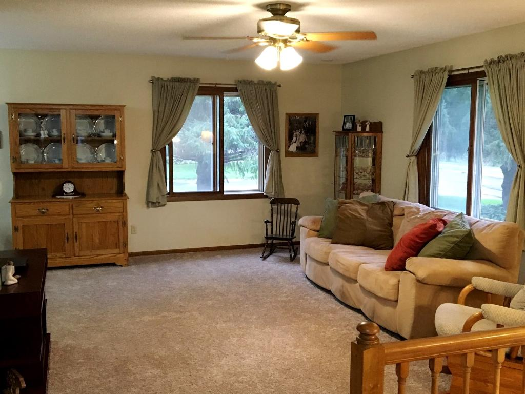 Spacious living area with neutral colors and ceiling fan. New carpet!