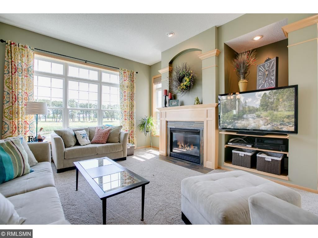 Great room features an inviting gas fireplace, soaring ceilings, and grand windows overlooking the serene pond and the greens of TPC.