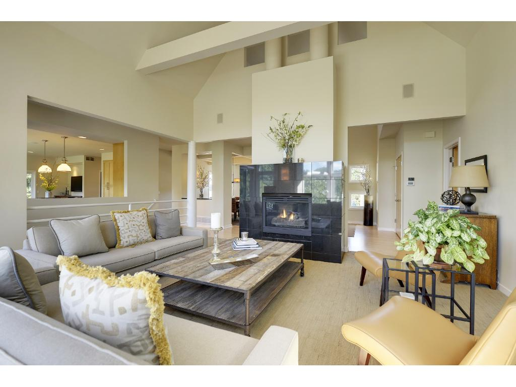 The formal living room features a dramatic gas fireplace, open views to the kitchen, foyer, and formal dining room. And don't forget those spectacular views.