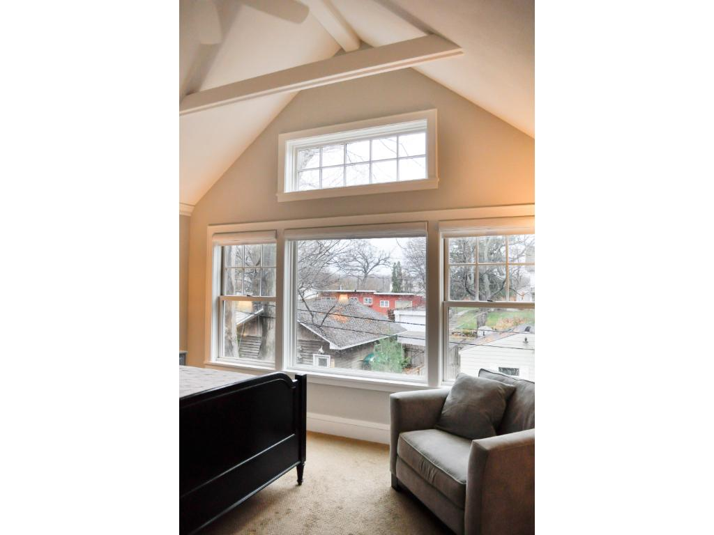 Another view of the master suite showing the large South facing windows, vaulted ceiling, and ceiling fan.