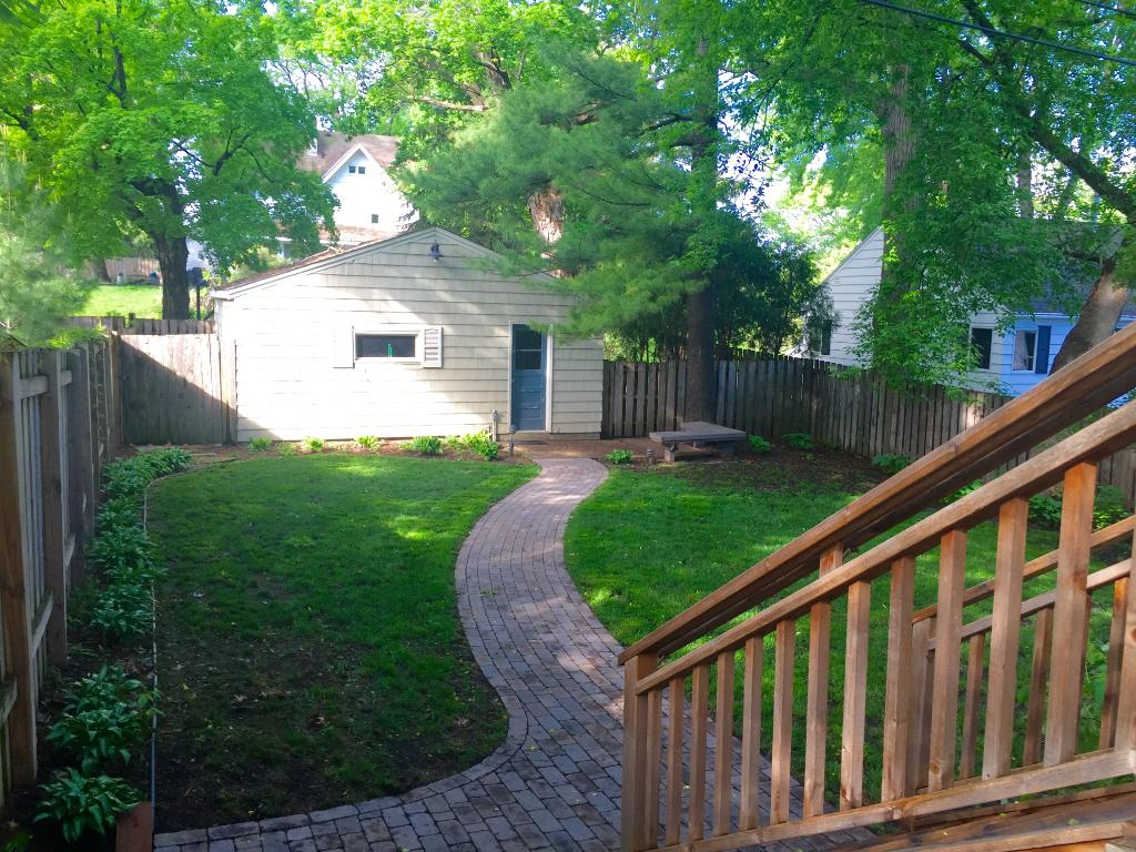 The private, fenced in backyard is newly landscaped with an irrigation system, perennials, and brick paver sidewalk leading to the 2 car detached garage.