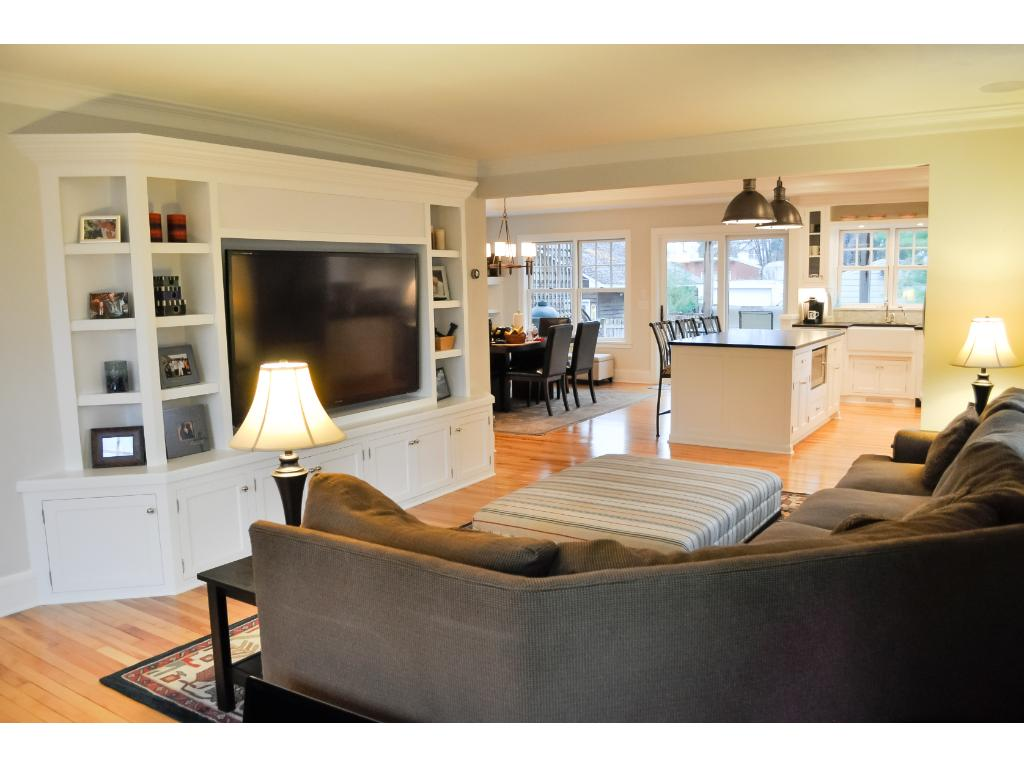 """The living room is open to the kitchen and dining room and features stunning reclaimed maple floors and enameled woodwork. A large, built-in custom cabinet with a 70"""" flat screen TV with home surround sound are included with the property."""