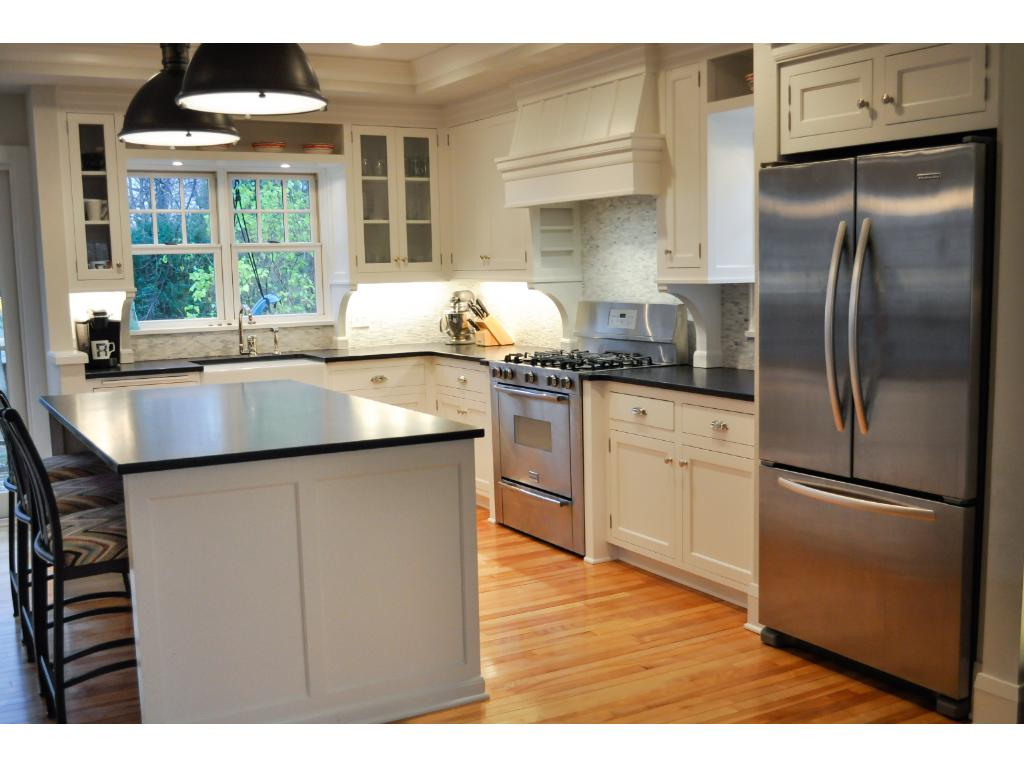 The chef's kitchen is bright and open with enameled custom cabinetry, honed granite, farm sink, high end fixtures, and stainless steel appliances.