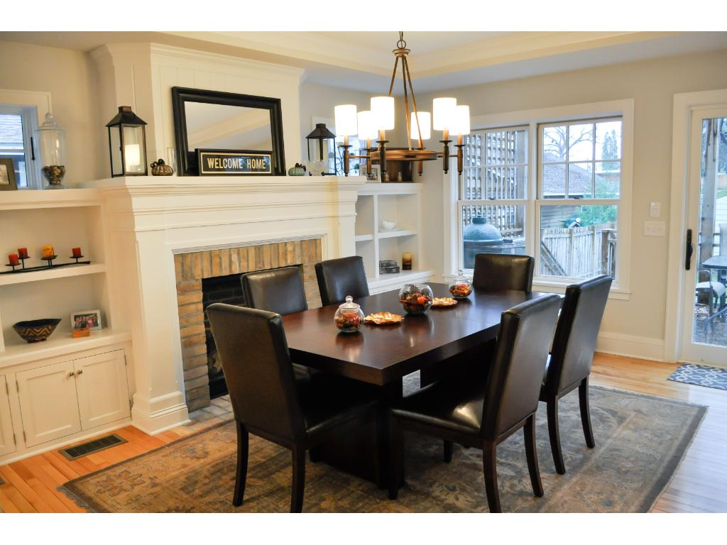 The dining room, which is open to the kitchen, has a gas fireplace with custom cabinetry and mantle along with a reclaimed Chaska common brick surround.
