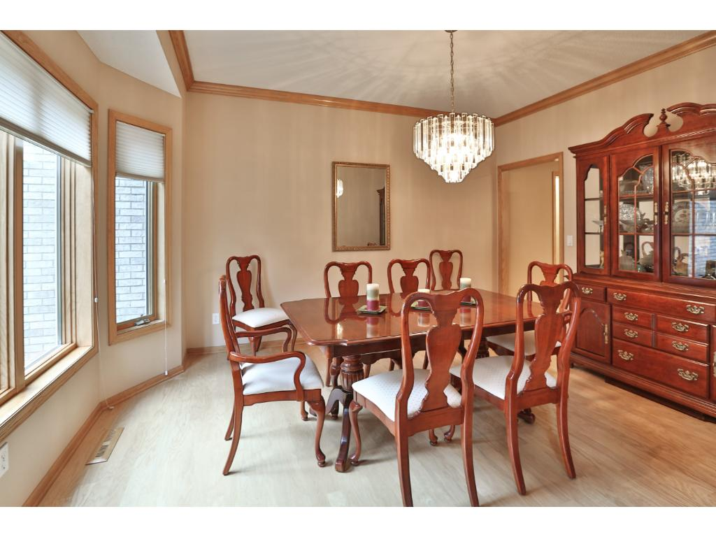 The formal dining room with hardwood flooring is also bayed and has a lovely view of the cup-de-sac island.