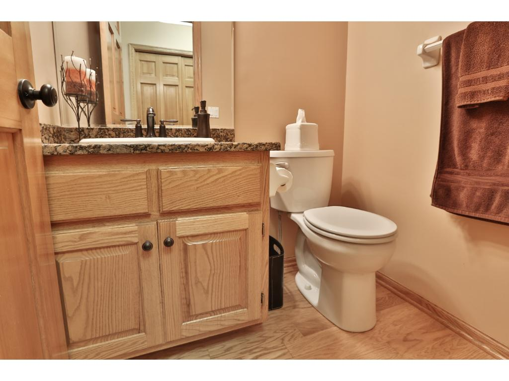 The convenient main floor half bath has a granite counter and new fixtures.  The laundry room is close by and boasts cabinets, a sink, window for fresh air, and pocket door for privacy.