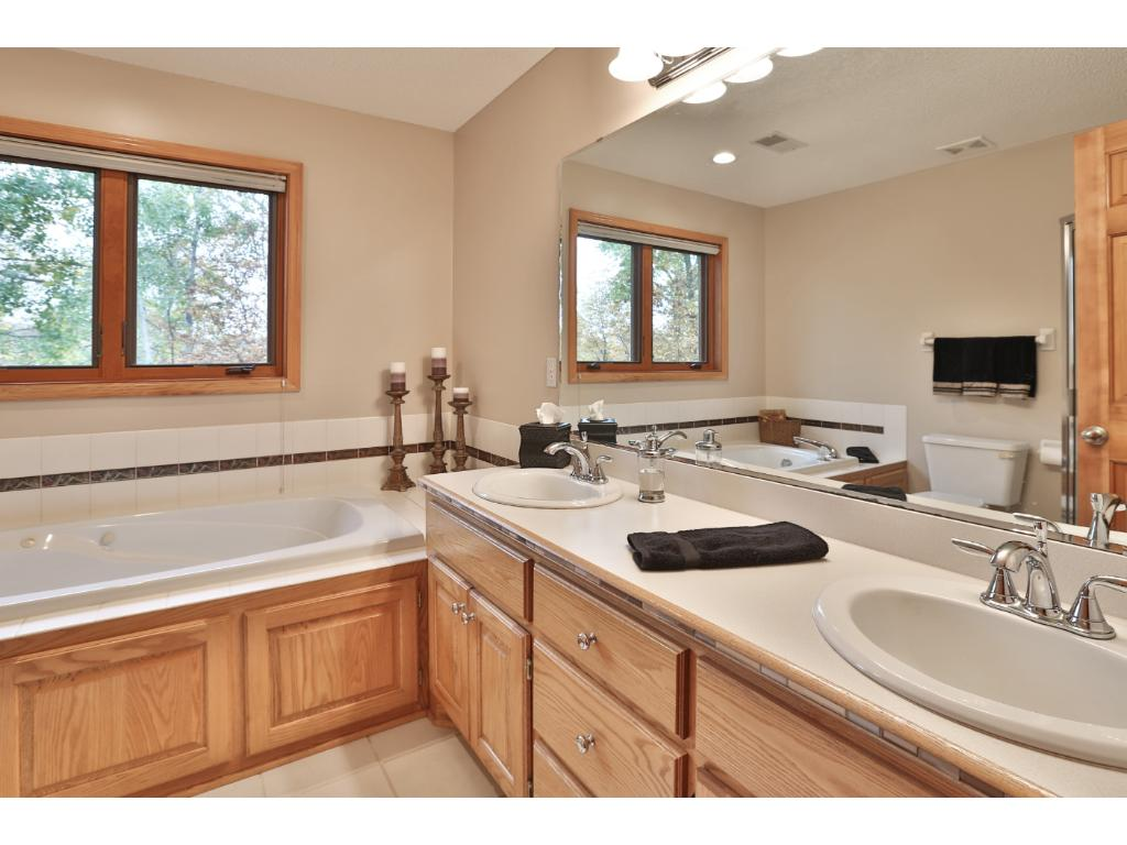 Large master bath has dual vanity, tile flooring, jacuzzi-type tub, separate shower, and large window overlooking the wooded back yard.  This a wonderful retreat!