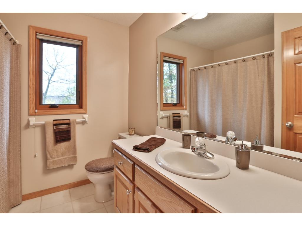 The full bath up has a neutral decor, tile floor and tub surround, and a window for natural light.