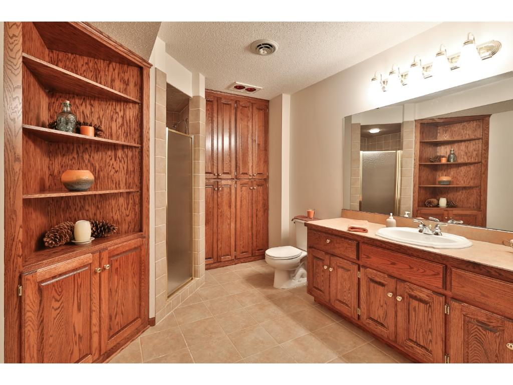The generous-sized lower level bath has a large vanity, walk-in shower, built-in shelving and cabinets, tile flooring, and a heat lamp.