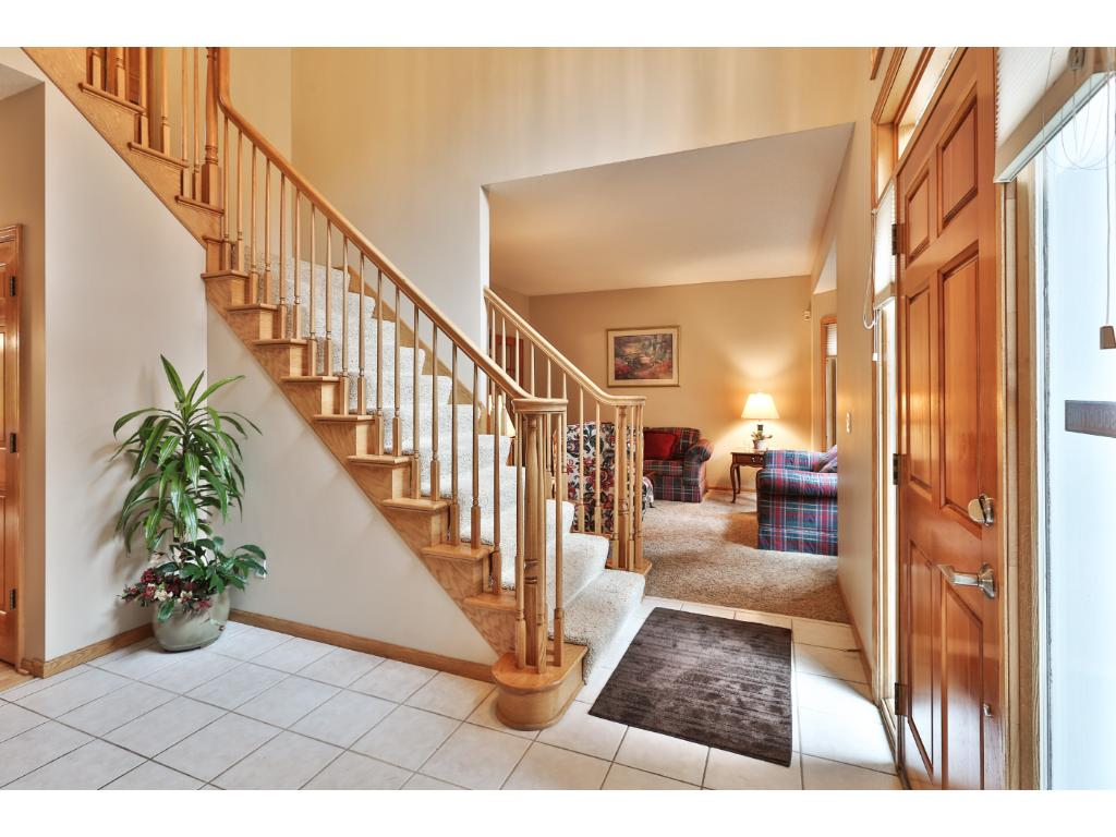 The light and bright 2-story foyer has a double closet for storage, and neutral tile flooring.