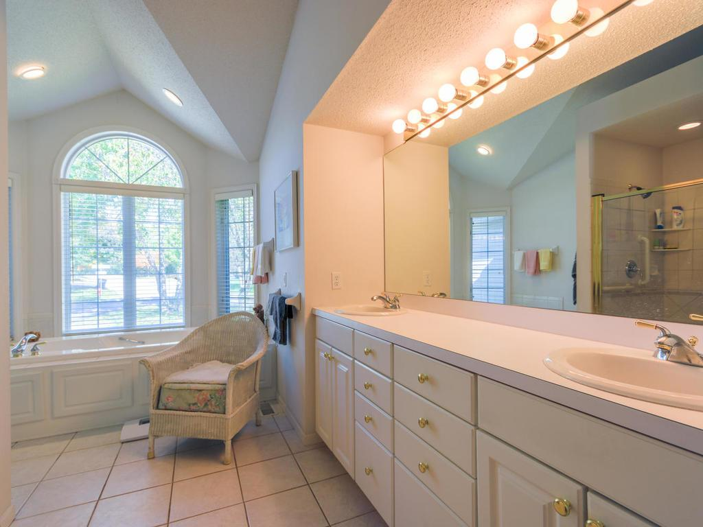 Main floor bathroom.  Double sinks.  Plenty of lighting.  Whirlpool tub. Windows to the front and side of home.