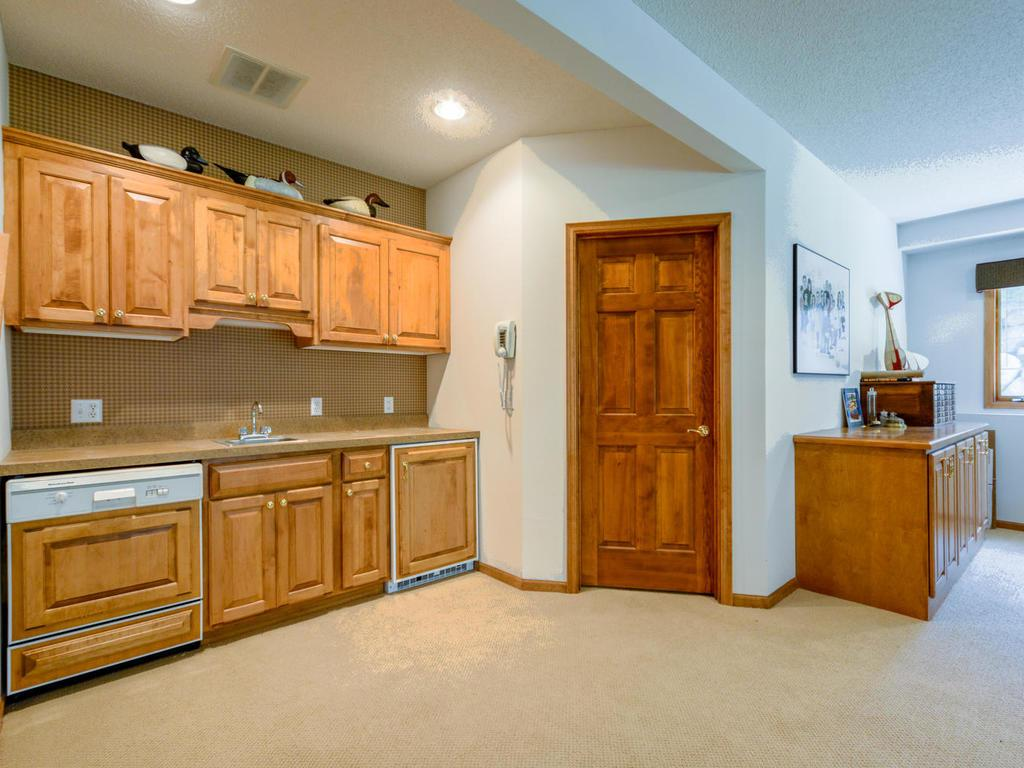 Lower level wet bar with dishwasher and small refrigerator.
