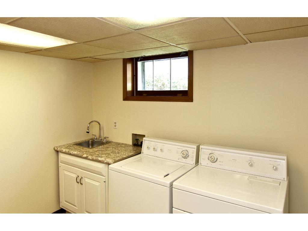 Finished laundry room with storage closet, folding counter & extra cupboard space!