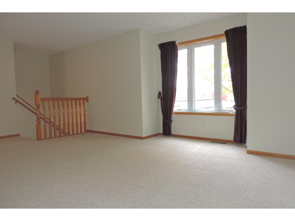 Spacious living room featuring brand new carpet and paint.
