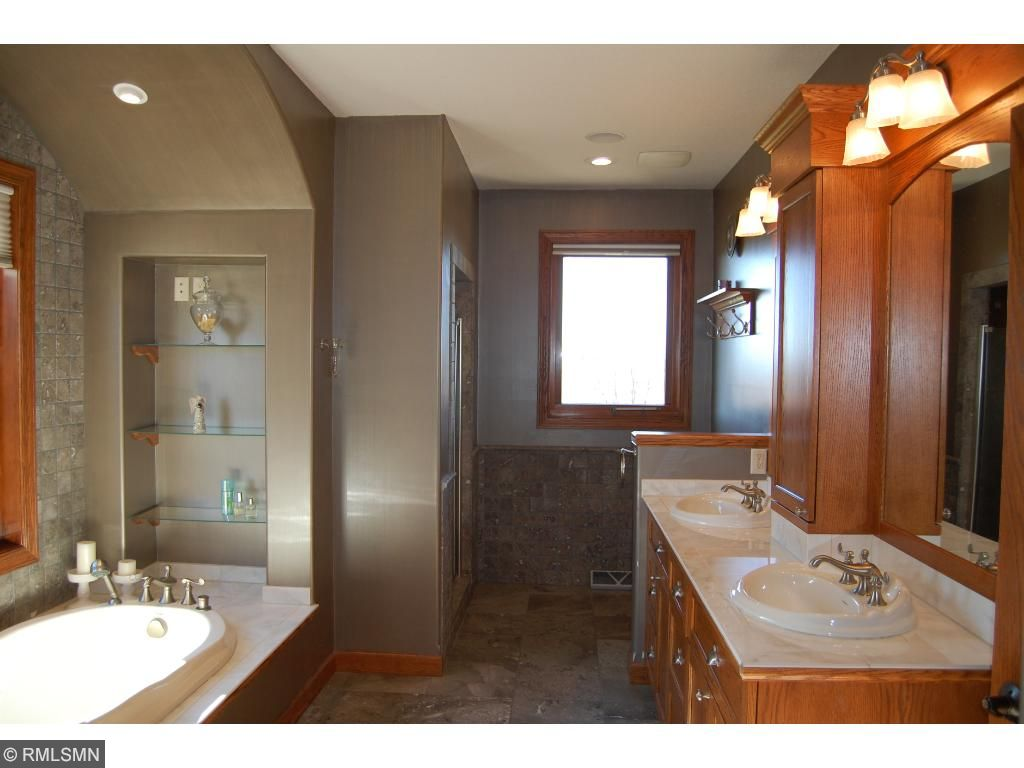 The master bathroom has a walk-in shower, tub, dual sinks, and beautiful marble tile flooring