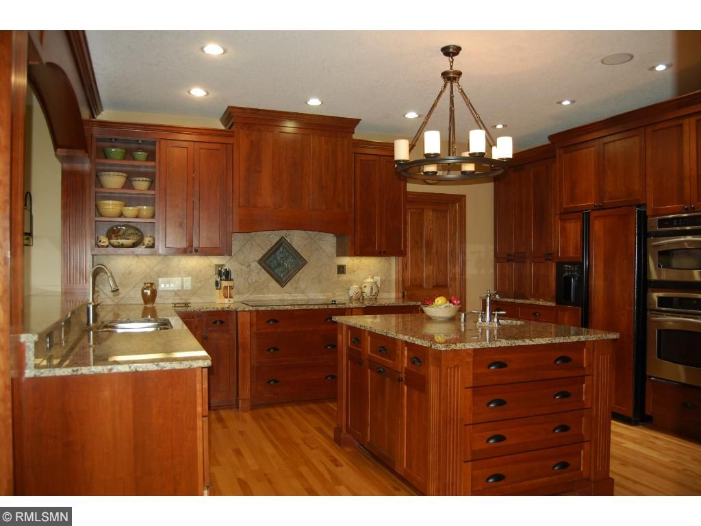 Granite countertops, custom cabinetry, wall oven, cooktop, and center island.