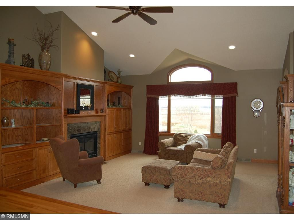 Living room has a high vaulted ceiling, large window, a fireplace, and custom built-ins