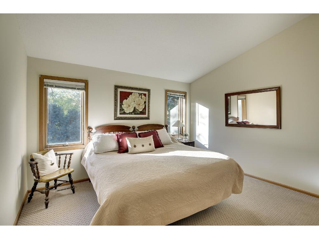 Serene light-filled main floor master bedroom with vaulted ceiling