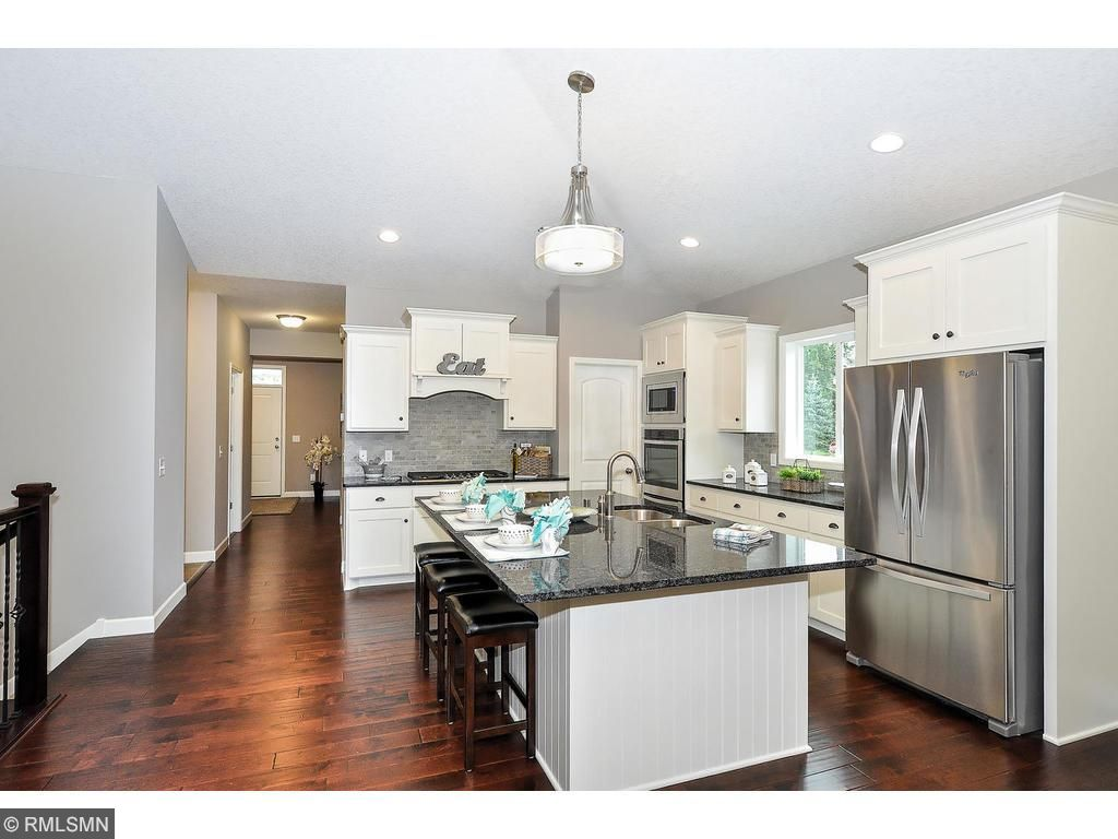 Gourmet Kitchen with Stainless Steel Appliance Package, Cooktop, Wall Oven and Wood Hood