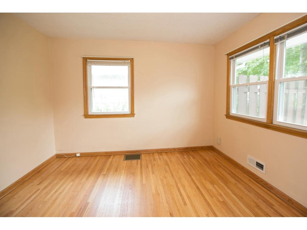 One of three main floor bedrooms with professionally refinished oak hardwood flooring