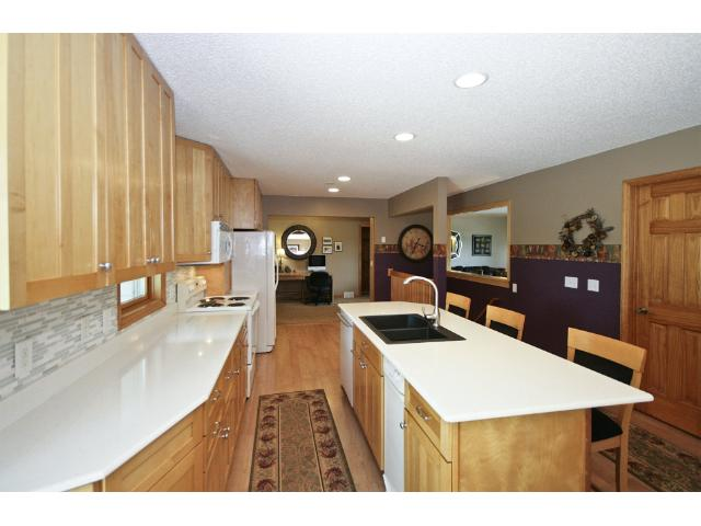 This view of the Kitchen showcases the beautiful maple cabinets, the center island with the breakfast bar seating area, and peers into the Living Room.