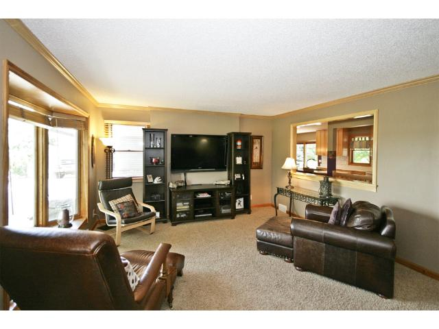 The 18x14 Living Room features a large bay window for lots of natural light, original oak hardwood floors hidden beneath the newer carpeting, and has a window cut-out into the Kitchen.