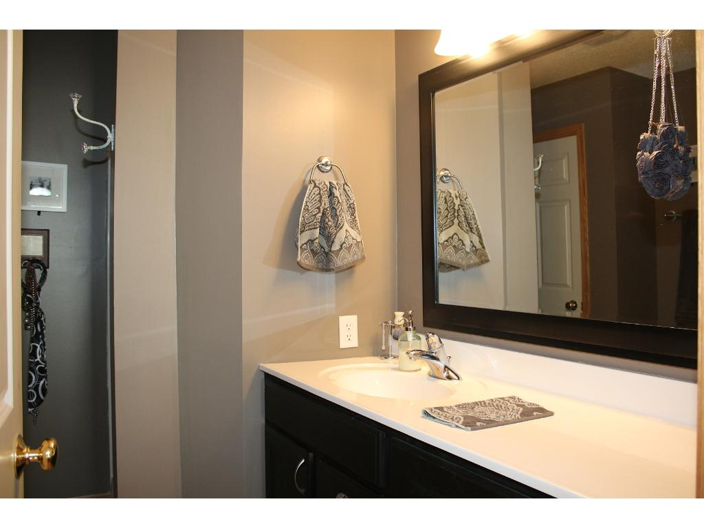 Well thought out master bathroom with a stand alone shower. The vanity has great counter space to the right of the sink for all your getting ready needs. Newer light fixture and mirror provide a modern look.