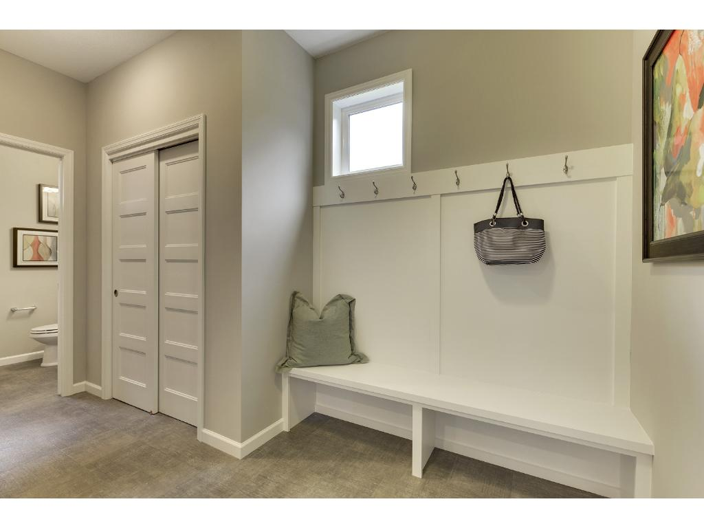 Large Mud Room from the garage with a bench and coat closet.