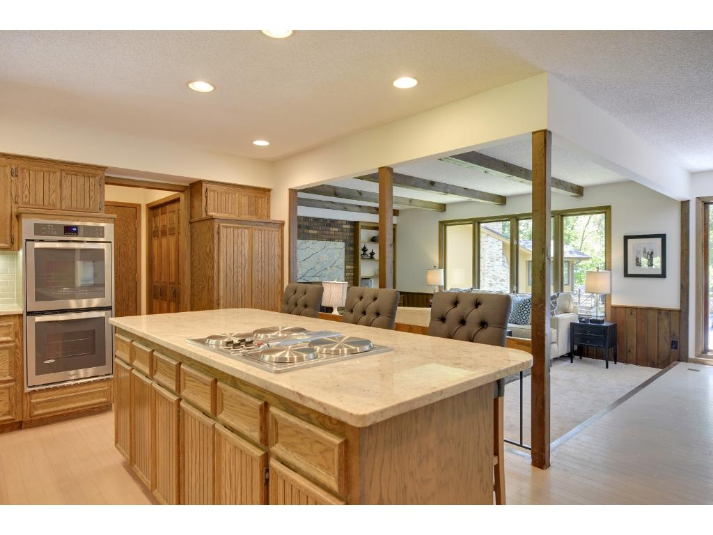Large Kitchen features tons of cabinetry & countertop space. Huge island w/breakfast bar & cooktop.