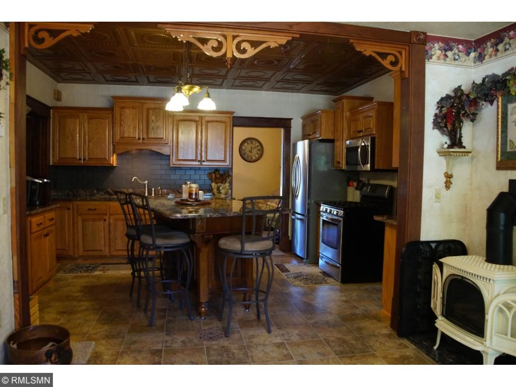 Gorgeous kitchen with granite island & stainless appliances.  Notice the free-standing fireplace in the formal dining area & the Back door entry.