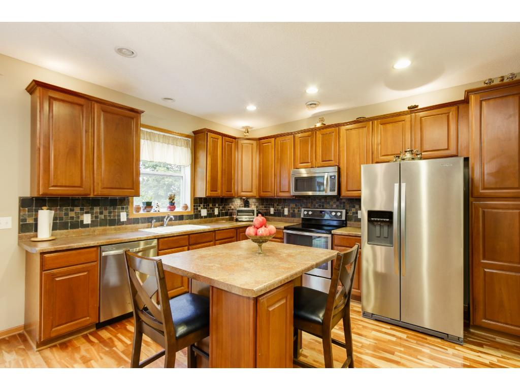 Big kitchen with an abundance of cabinets, newer stainless steel appliances and center island.