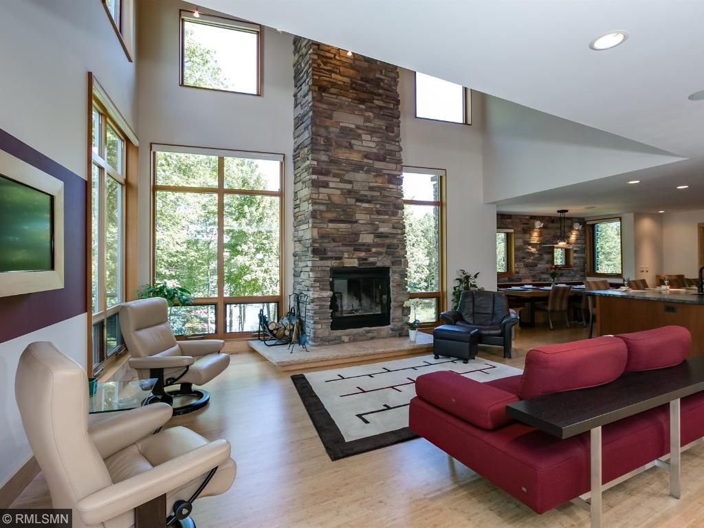 Two story living room with wood burning fireplace.