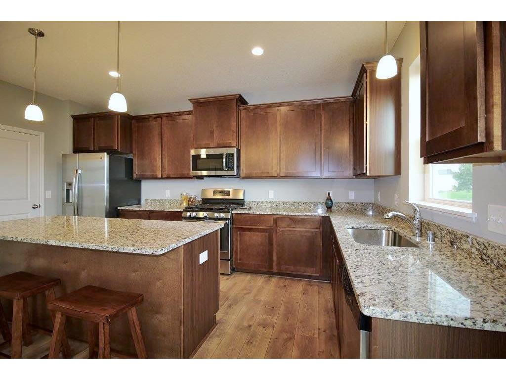 Additional view of this gorgeous kitchen coated in granite and stainless appliances.