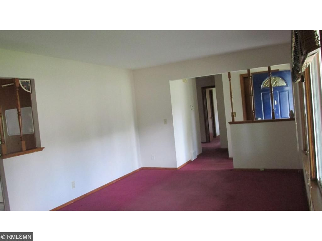Living room with carpet.  Large window.  Circular floor plan.  Open to dining room on one end.  Front door on the other end and hallway to bedrooms.