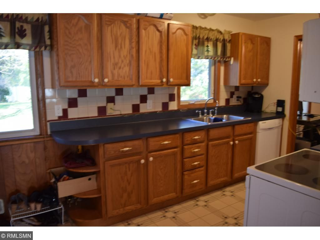 Tile back splash.  Kitchen window.  Extra decorative shelves at the end of the counter.  Open floor plan to dining room.   Walk through the other end of the kitchen to the den.