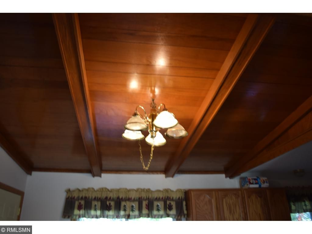 Dining area wood ceiling with beams.