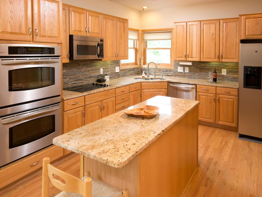This kitchen has it all- stainless steel appliances includes double wall ovens, built-in microwave, dishwasher, side by side fridge freezer with water & ice, under cabinet lighting, granite counter tops, functional island with additional storage.