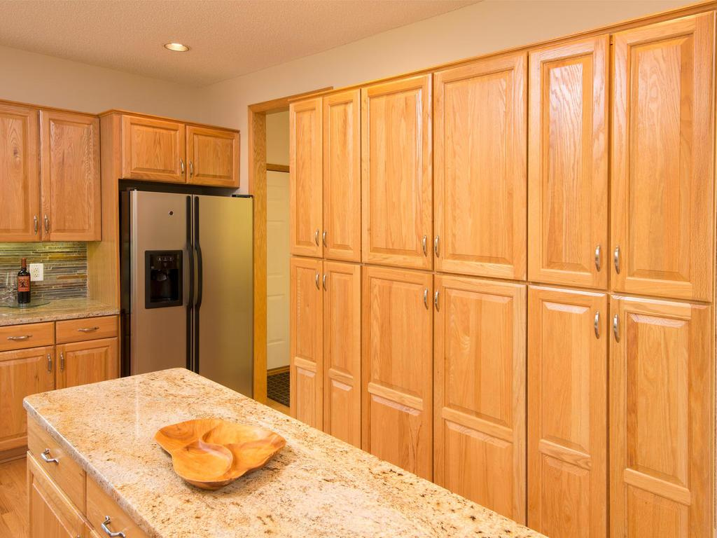 You will love the storage found in this kitchen. A wall of cabinetry for all your storage needs. Great flow from the garage to the kitchen for ease of bringing in groceries. Always refreshing coming home to this sun filled room.
