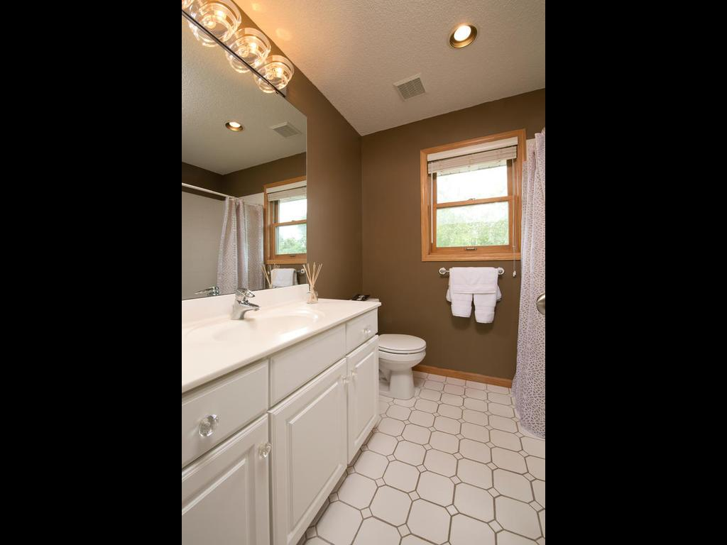 This upper level full bathroom provides a spa like experience with its whirlpool tub that only needs to be shared with two bedrooms. The large vanity allows plenty of space to get ready and there is an extra linen closet behind the door for storage.