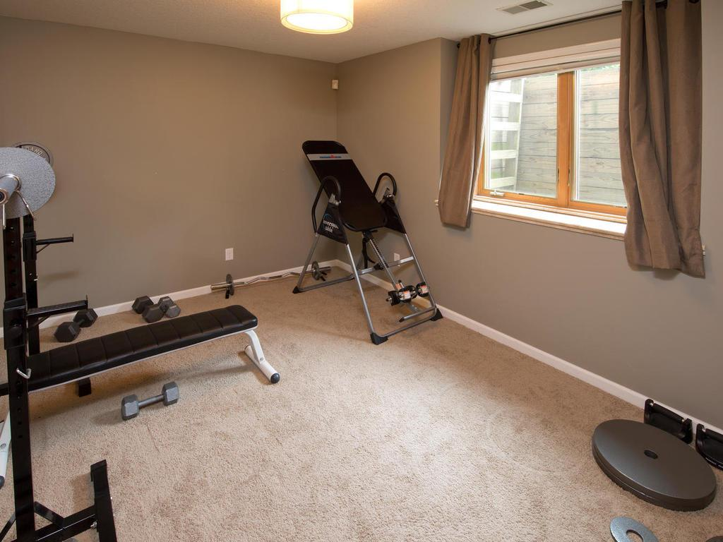 Workout room, guest suite, playroom, or just a great fourth bedroom in the lower level. Natural light and large closet make this bedroom highly desirable. Straight across the hall is a beautiful 3/4 bath helping to create that private bedroom space.