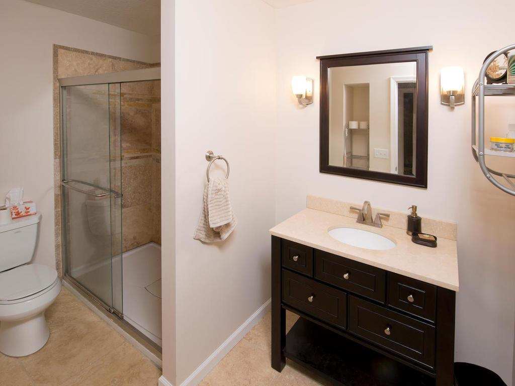 Updated lower level 3/4 bath is gleaming with an oversized vanity, tiled floor, and tiled shower surround. While entertaining in the lower level there is no need to go upstairs.